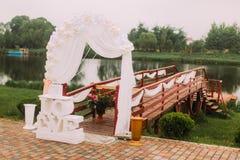 La composizione di nozze dei segni e dell'arco disposti vicino al pilastro di wooeden Immagini Stock Libere da Diritti