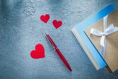 La composizione di scrittura d'annata della penna a sfera rossa dei cuori prenota sopra Immagini Stock