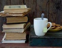 La composizione di una pila di vecchi libri, di tazze di tè, di vetri e di piatti dei biscotti di zucchero su un fondo di legno F Immagini Stock Libere da Diritti