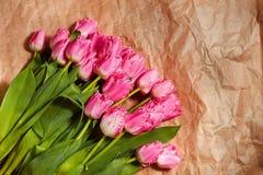 La composizione nel fiore fresco, tulipani rosa del mazzo sul mestiere incarta il fondo Biglietto di S. Valentino, ` s delle donn Fotografia Stock Libera da Diritti