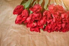 La composizione nel fiore fresco, tulipani rossi del mazzo sul mestiere incarta il fondo Biglietto di S. Valentino, ` s delle don Fotografia Stock Libera da Diritti