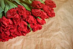 La composizione nel fiore fresco, tulipani rossi del mazzo sul mestiere incarta il fondo Biglietto di S. Valentino, ` s delle don Immagine Stock Libera da Diritti
