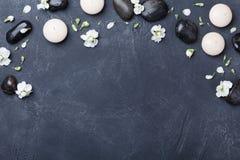 La composizione nella stazione termale ed in aromaterapia ha decorato i fiori sulla vista superiore del fondo di pietra nero Trat immagine stock libera da diritti