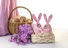 La composizione in Pasqua con le uova in un canestro di vimini, nei giocattoli divertenti ed in un campo fiorisce Immagini Stock Libere da Diritti