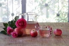 La compota de Apple en un jarro transparente, manzanas y un ramo de subió Fotos de archivo