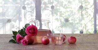 La compota de Apple en un jarro transparente, manzanas y un ramo de subió Imagen de archivo libre de regalías