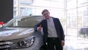 La compra auto, hombre joven del comprador con los vidrios con mucho gusto frota ligeramente el nuevo coche y da gesto positivo almacen de video