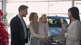 La compra auto, los pares jovenes con la muchacha del niño aconseja con el vendedor del coche en la compra del vehículo de la fam metrajes