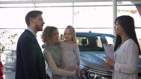 La compra del automóvil de la familia, el marido del consumidor joven y la esposa con poco niño comunican con el concesionario de almacen de video