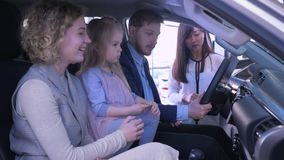La compra del transporte de la familia, los pares jovenes con la muchacha linda del niño comunica sobre el coche de la compra con almacen de metraje de vídeo