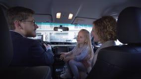 La compra del transporte de la familia, padre con la madre con la muchacha dulce del pequeño niño que da los pulgares encima del  metrajes