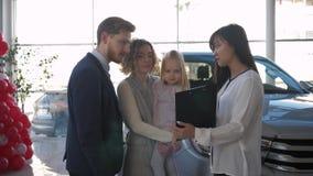 La compra del vehículo, pareja feliz con el pequeño niño informa con el consultor del coche en la compra del automóvil de la fami almacen de video
