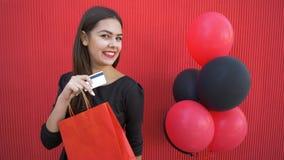 La compra en línea en viernes negro, la hembra atractiva con el dinero electrónico y las compras encantan descuentos metrajes