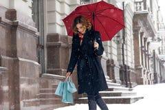 La compra hermosa de la calle de la nieve de la mujer presenta a Navidad Año Nuevo Fotos de archivo libres de regalías