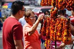La compra madura de la mujer ensartó las flores eternas del vendedor ambulante de la calle en una yarda de la iglesia fotos de archivo