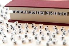 La comprensione di parola scritta con le lettere fra un libro impagina il fondo bianco con le lettere sparse intorno al concetto  Immagini Stock