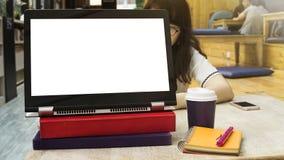 La compressa in bianco dello schermo della copia sul computer è disposta sul libro di testo Fotografie Stock