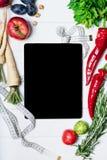 La compressa con nastro adesivo, i rosmarini, una radice, i pomodori ciliegia, i peperoni ed i dadi di misurazione su una vista s fotografia stock libera da diritti