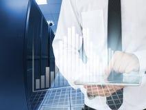 La compressa di uso dell'uomo di affari per analizza nel centro dati Fotografia Stock