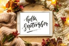 La compressa dice la parola ciao settembre con le foglie rosse e una pedana sui precedenti di legno Concetto dell'autunno illustrazione di stock
