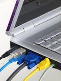La computadora portátil con el color del muliti enchufado vira hacia el lado de babor Foto de archivo libre de regalías