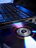 La computadora portátil con un disco compacto del colorfull Foto de archivo libre de regalías