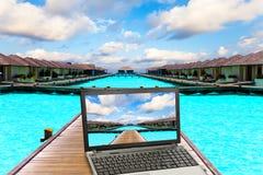 La computadora portátil en una playa Imagen de archivo libre de regalías
