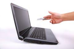 El ordenador portátil y la mano dan la tarjeta de crédito Imagen de archivo libre de regalías