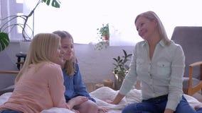 La comunicación de la diversión con la madre, mamá feliz querida con las hijas se divierte que charlan y que cuelgan hacia fuera