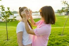 La comunicación del padre y adolescente, madre se divierte con su hija Césped verde, reconstrucción y entretenimiento del fondo imágenes de archivo libres de regalías