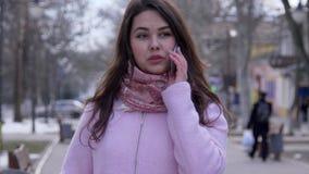 La comunicación móvil, muchacha alegre habla por el teléfono celular en el primer de la calle encendido almacen de metraje de vídeo
