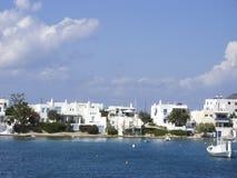 La comunità tipica della spiaggia con Cicladi disegna il doo bianco del blu della casa Immagine Stock