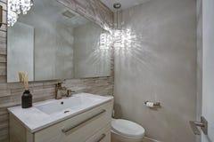La conception contemporaine de salle de bains avec les tuiles linéaires de taupe accentuent le mur images libres de droits
