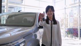 La concesión de coche, retrato de la mujer asiática del trabajador feliz del taller mecánico acaricia al vehículo con llaves del  metrajes