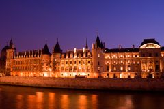 La Conciergerie. Twilight view of the Conciergerie (old medieval jailhouse) and the Seine river - Paris, France stock image
