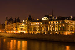 La Conciergerie. Night view of the Conciergerie (old medieval jailhouse) and the Seine river - Paris, France royalty free stock images
