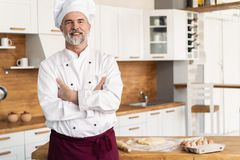 La condizione caucasica attraente del cuoco unico con le armi ha attraversato in una cucina del ristorante fotografie stock libere da diritti