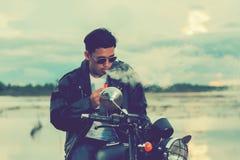 La condizione dell'uomo del motociclista fuma con la sua motocicletta accanto al lago naturale e bello, godendo della libertà e d Immagine Stock Libera da Diritti