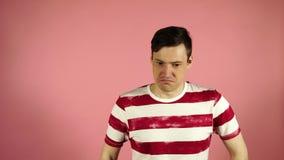 La condizione dell'uomo isolata su fondo rosa che guarda la macchina fotografica non dice non archivi video