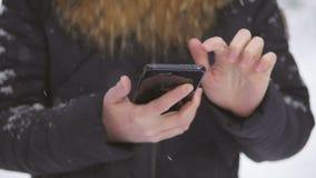 La condizione della donna nell'ambito delle precipitazioni nevose utilizza un telefono cellulare per chiamare ed usare Internet video d archivio