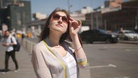 La condizione della ragazza alla strada che aspetta l'arrivo di un taxi stock footage