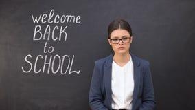 La condizione deludente infelice dell'insegnante vicino alla lavagna, dà il benvenuto a di nuovo a scuola stock footage