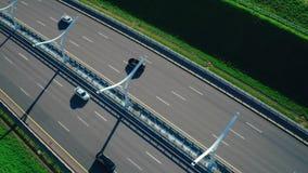 La conducción de automóviles en la carretera moderna en ciudad del fondo ajardina la visión aérea almacen de metraje de vídeo