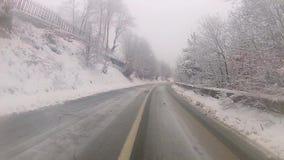 La conducción en la niebla del invierno cubrió la carretera de asfalto de la montaña metrajes