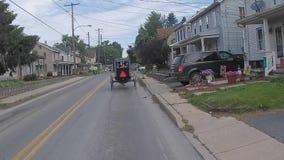 La conducción a lo largo del campo de Amish pareció un caballo y un cochecillo con los niños de Amish en la parte posterior almacen de metraje de vídeo