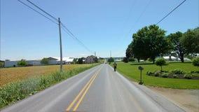 La conducción a lo largo del campo de Amish pareció a un hombre de Amish en una vespa almacen de video