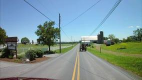 La conducción a lo largo del campo de Amish pareció un hombre de Amish y un tractor de granja del vintage almacen de metraje de vídeo