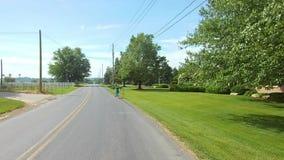 La conducción a lo largo del campo de Amish pareció a una muchacha de Amish en una vespa almacen de video