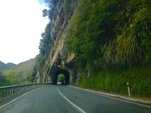 La conduite sur la route dans le tunnel a découpé la roche de la montagne Photo stock