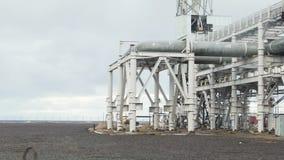 La conduttura industriale ha costruito vicino alla spiaggia Grande raffineria di petrolio vicino al mare in una mattina nuvolosa  stock footage